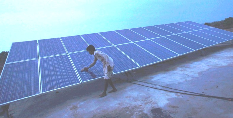 indian guy cleaning the solar panels barefoot